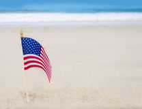 Patriotic USA background with American flag. On the sandy beach Royalty Free Stock Images