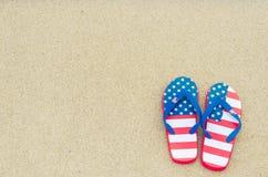 Patriotic USA background on the sandy beach. Patriotic USA background with flip flops on the sandy beach stock photos