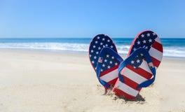 Patriotic USA background on the sandy beach. Patriotic USA background with flip flops and decorations on the sandy beach royalty free stock photos