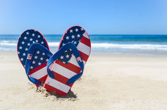 Patriotic USA background on the sandy beach. Patriotic USA background with flip flops and decorations on the sandy beach royalty free stock photography