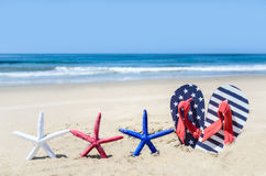 Patriotic USA background with starfish on the sandy beach. Patriotic USA background with starfishes and flip flops on the sandy beach stock image