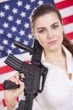 Patriotic woman with gun over american flag Stock Image