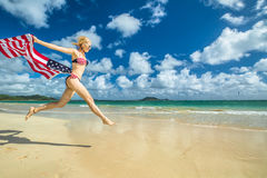 Patriotic woman jumping. Patriotic smiling woman with american flag bikini weaving american flag. Female jumping in tropical Hawaiian beach. Lanikai Beach in Royalty Free Stock Image