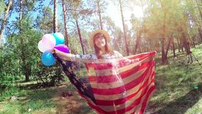 Patriotic woman smile with USA flag and balloons, America independent day. Happy patriotic woman smile with USA flag and balloons, national independent day of stock footage