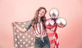Patriotic girl with the flag of America on a colored background. Patriotic young beautiful girl with the flag of America and balls on a colored background stock photos