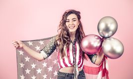 Patriotic girl with the flag of America on a colored background. Patriotic young beautiful girl with the flag of America and balls on a colored background royalty free stock image