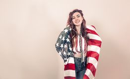 Patriotic girl with the flag of America on a colored background. Patriotic young beautiful girl with the flag of America on a colored background, concept of stock images