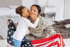 Patriotic young lady happy being home. Sweet home. Tender caring beautiful women feeling emotional while being kissed by her daughter and holding a flag in her stock images