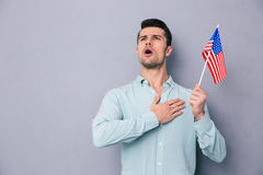 Patriotic young man holding US flag. Over gray background Stock Image