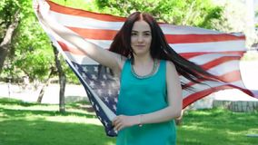Patriotic  young woman with the American flag held stock video footage