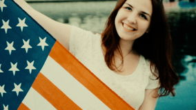 Patriotic young woman holds American Flag in front of her body while standing on the beach, grainy damaged old footage. Heritage concept, patriotic young woman stock footage