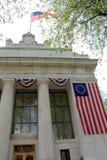 Patriotische Flaggen, die von der großen Steinfront von Adirondack-Treuhandbank, Saratoga, New York, 2015 hängen Lizenzfreie Stockfotografie