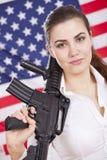 Patriotische Frau mit Gewehr über amerikanischer Flagge Stockbild