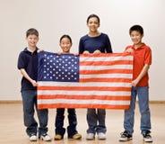 Patriotische Kinder, welche die amerikanische Flagge halten Lizenzfreies Stockfoto