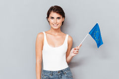 Patriotische lächelnde Frau, die europäische Flagge über Grau hält Lizenzfreie Stockbilder