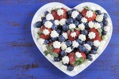 Patriotische rote, weiße und blaue Beeren mit frischer Schlagsahne spielt mit Kopienraum die Hauptrolle Stockbild