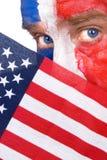 Patriotischer Mann, der über einer amerikanischen Flagge blickt Stockbild