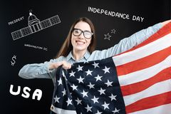 Patriotischer Student, der eine Flagge der USA beim Feiern des Unabhängigkeitstags hält Stockbilder