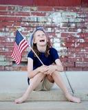 Patriotisches kleines Mädchen mit Flagge auf Beschränkung Lizenzfreie Stockfotografie