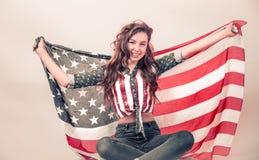 Patriotisk flicka med flaggan av Amerika p? en kul?r bakgrund royaltyfri fotografi