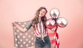 Patriotisk flicka med flaggan av Amerika p? en kul?r bakgrund arkivfoton