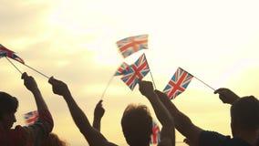 Patriotisk UK-folkmassa som utomhus vinkar med flaggor arkivfilmer