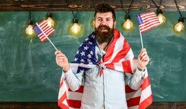 Patriotiskt utbildningsbegrepp Den amerikanska läraren vinkar med amerikanska flaggan Mannen med skägget och mustaschen på lyckli Arkivfoto