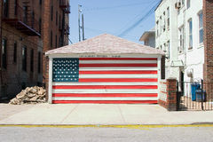 Patriotism. American flag painted over the garage door royalty free stock images