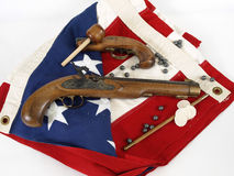Patriotism. Two antique muzzel loader guns displayed over a US flag. Over a white background Stock Image