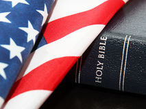 Patriotism and Faith. A Holy Bilbe draped by a US or American flag.  A concept of faith and patriotism or the controversy of the separation of states and Stock Photos