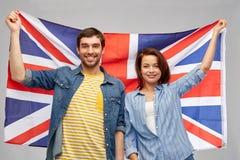 Happy couple holding british flag. Patriotism and national concept - happy couple holding british flag over grey background royalty free stock images