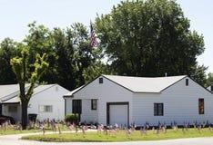 Patriotismo extremo - pequeña casa blanca con cientos banderas americanas en la yarda imagen de archivo