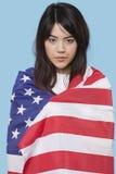 Patriottische jonge die vrouw in Amerikaanse vlag over blauwe achtergrond wordt verpakt Royalty-vrije Stock Fotografie