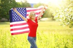 Patriottische jonge vrouw met Amerikaanse vlag Stock Foto's