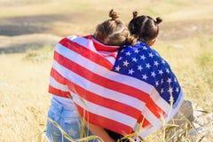 Patriottische vakantie Gelukkige jonge geitjes, leuke kleine kinderenmeisjes met Amerikaanse vlag De V.S. vieren 4 van Juli royalty-vrije stock afbeelding