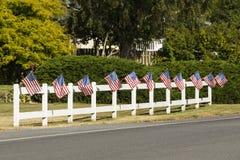 Patriottische vertoning van Amerikaanse vlaggen die op witte piketomheining golven naast een weg Typische kleine stad de V.S. vie royalty-vrije stock fotografie
