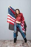 Patriotyczna dziewczyna jest ubranym czerwoną skórzaną kurtkę i trzyma usa flaga Zdjęcia Royalty Free
