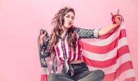 Patriotyczna dziewczyna z flagą Ameryka na barwionym tle obraz stock