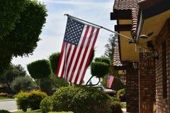 Patriotyczne flaga amerykańskie wiesza od okolicznych domów fotografia royalty free