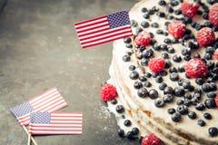 Patriotyczny flaga amerykańska tort z czarnymi jagodami i truskawkami na rocznika bielu tle Zdjęcia Royalty Free