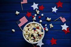 Patriotyczny popkorn na Lipu 4 w białym wiadrze z flagą amerykańską na błękitnym drewnianym tle USA dzień niepodległości obrazy royalty free
