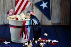 Patriotyczny popkorn na Lipu 4 w białym wiadrze z flagą amerykańską na błękitnym drewnianym tle USA dzień niepodległości obraz stock