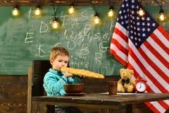 Patriotyzm i wolność Chłopiec je chleb przy flaga amerykańską przy wiedza dniem Szkolny dzieciak przy lekcją w 4th Lipiec fotografia stock