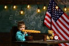 Patriotyzm i wolność Szkolny dzieciak przy lekcją w 4th Lipiec Popiera szkoła lub stwarza ognisko domowe uczyć kogoś Chłopiec je  zdjęcia royalty free