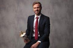 Patrocine o homem de negócios que guarda seu copo do troféu e sente-se foto de stock royalty free