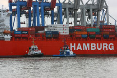 A patrol boat and a towboat are working next to the cargo ship of the German shipping company `Hamburg Sud`. Stock Photo