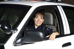 Patrol car. A female police officer sitting in her patrol car during a night shift Royalty Free Stock Photos