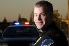 Patrol cop. A smiling police officer standing in front of his patrol car Royalty Free Stock Image