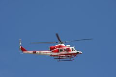 Patrol helicopter of firefighters in blue sky over a fire Royalty Free Stock Images