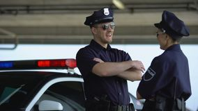 Patrol officers discussing shift and laughing standing near police car, law. Stock footage stock video